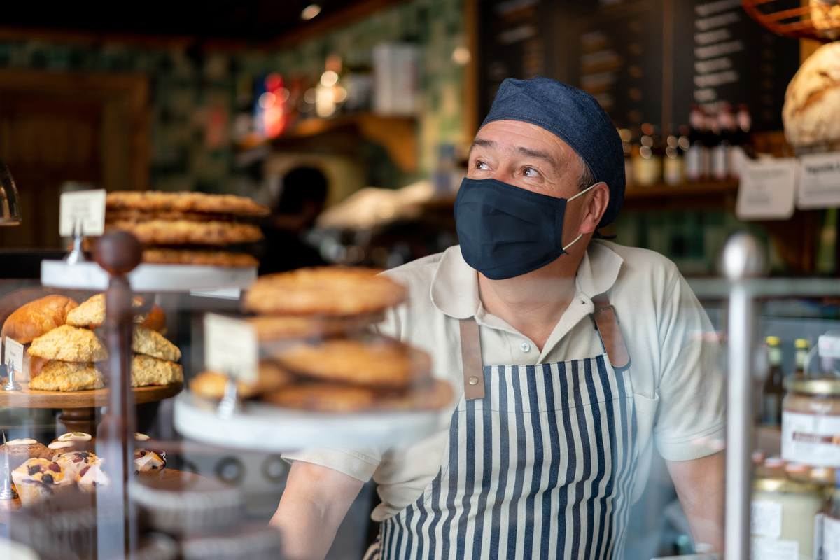 Restaurant owner wearing a face mask stands behind counter.